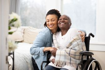 A woman embracing an elderly woman in a wheelchair