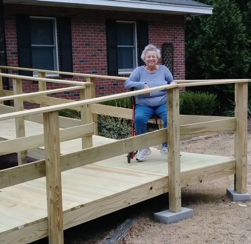 Older woman smiling in a wheelchair on a ramp