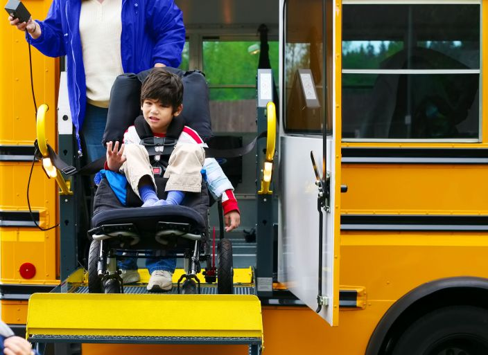 Child on a wheelchair ramp exiting a school bus