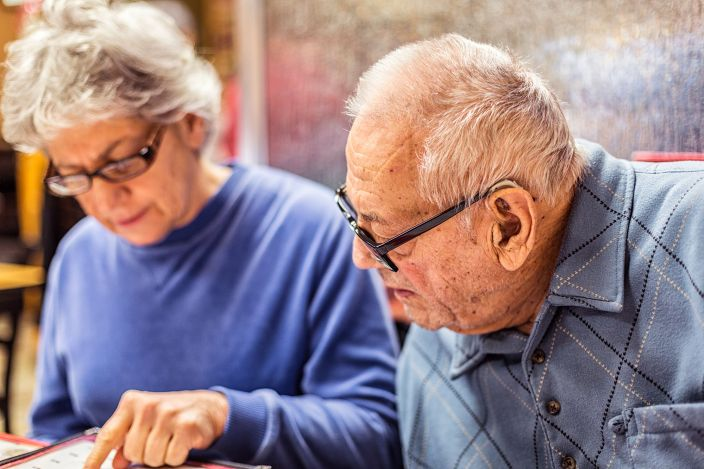 Elderly couple reading a menu