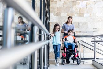 Daughter, mom, and son in a wheelchair on a walkway