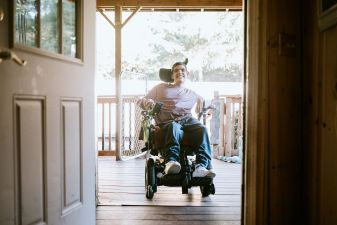 A teenage boy in a wheelchair on  a deck, smiling through an open door