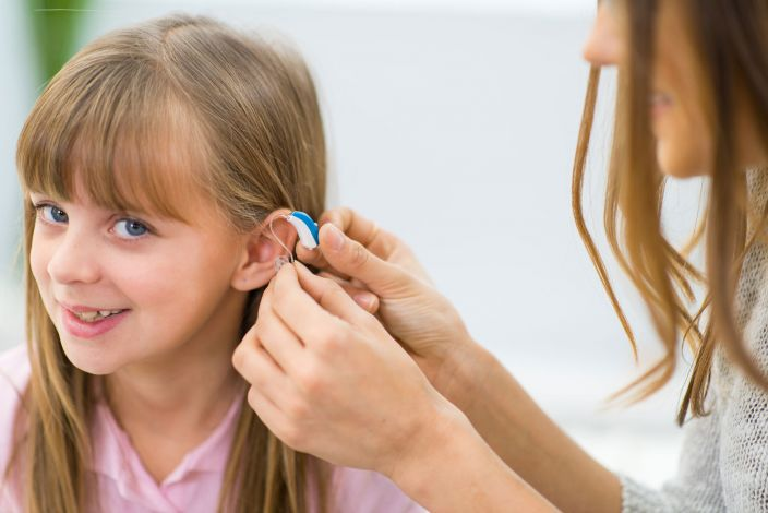 A woman putting a hearing aid on for a young girl