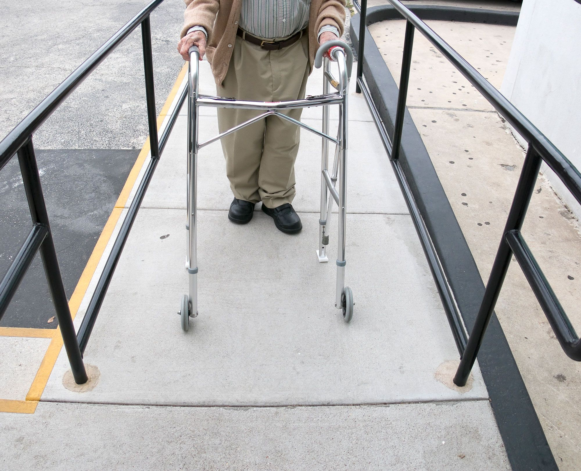 Elderly man with a walker walking up a ramp